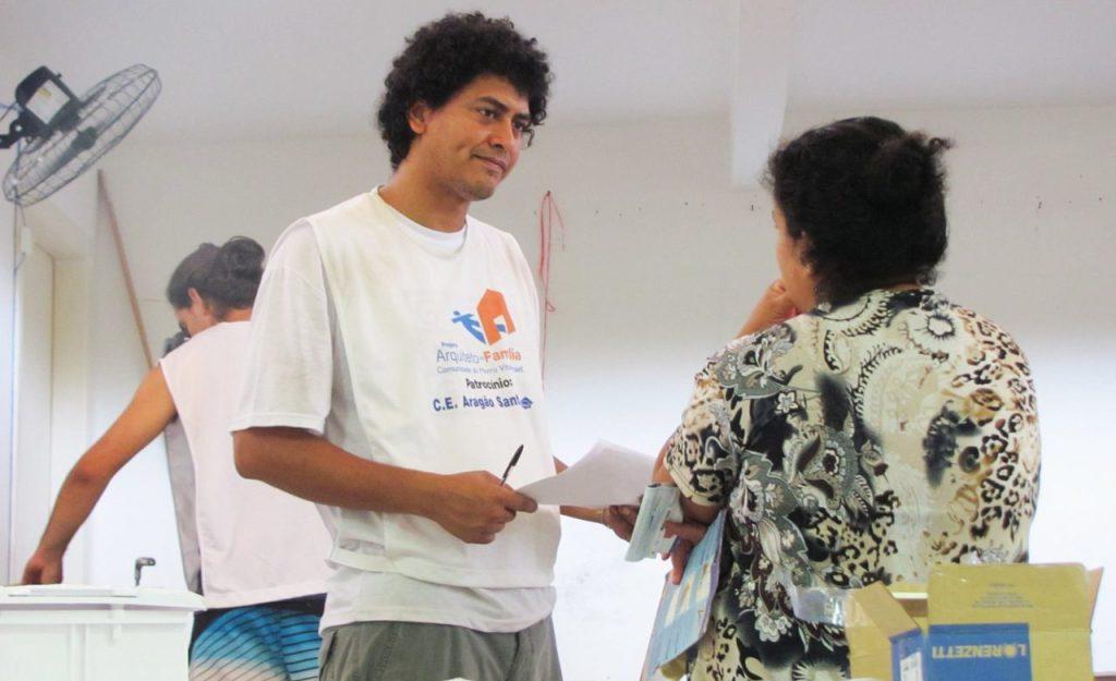 Voluntário do Arquiteto de Família com moradora no Morro Vital Brasil, em Niterói (RJ), área de concentração do projeto