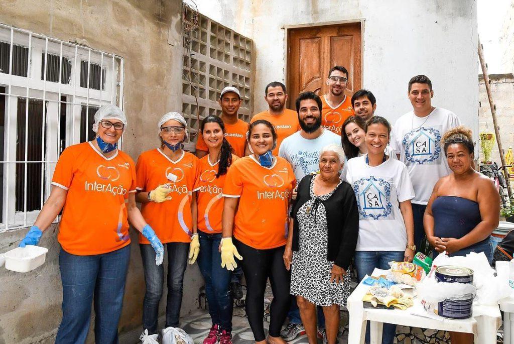 A dona de casa Carmosina Bispo e os colaboradores do projeto Adote uma Casa