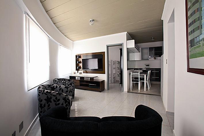Interior de um dos apartamentos: sala tem três janelas